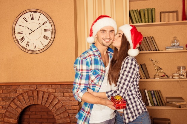Glückliches junges mädchen, das ihren freund mit geschenk in den weihnachtsmützen küsst