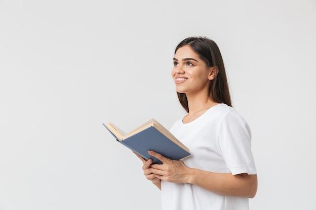 Glückliches junges mädchen, das isoliert auf weiß steht und ein buch liest