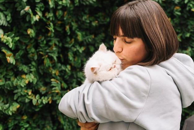 Glückliches junges mädchen, das mit ihrer katze aufwirft
