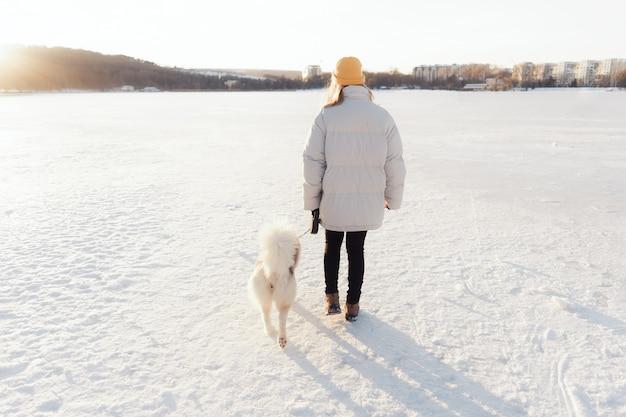 Glückliches junges mädchen, das mit siberian husky hund im winterpark spielt