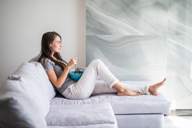 Glückliches junges mädchen, das müsli mit früchten von einer schüssel isst, die auf einer couch zu hause sitzt