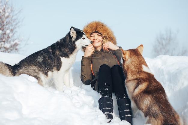 Glückliches junges mädchen, das rote und schwarze schlittenhunde im winter umarmt