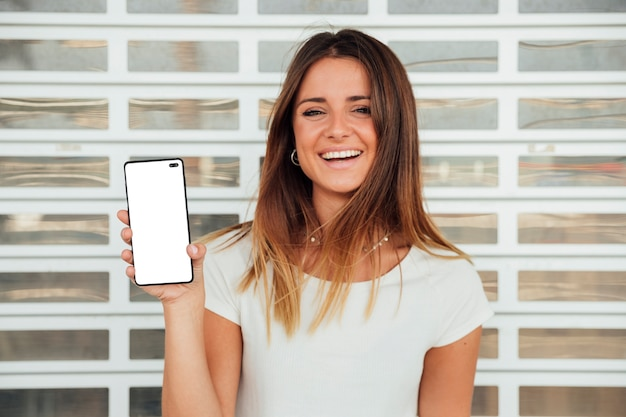 Glückliches junges mädchen, das smartphone hält