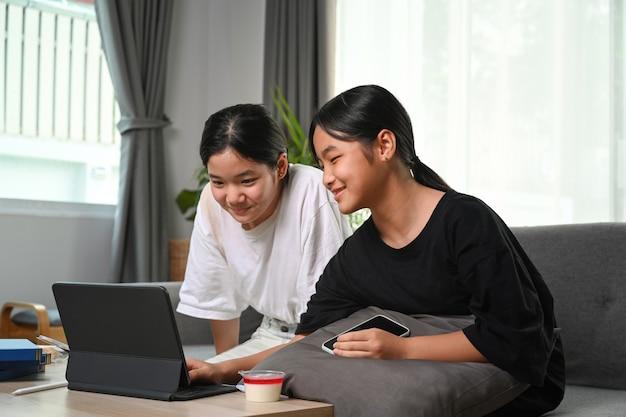 Glückliches junges mädchen genießen wochenende mit ihrer freundin und video auf computer-tablet zu hause