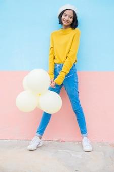 Glückliches junges mädchen halten gelben ballon tragen gelbes pulloverlächeln über blauem hintergrund.