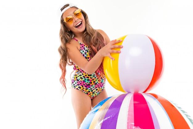 Glückliches junges mädchen im badeanzug, sonnenbrille, kappe mit gummibällen lächelt lokalisiert auf einem weißen hintergrund
