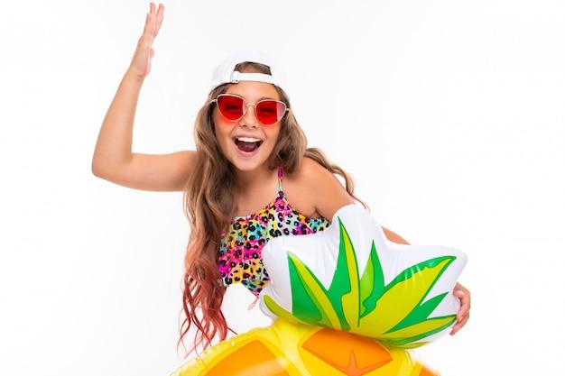 Glückliches junges mädchen im badeanzug, sonnenbrille, kappe mit gummiring lokalisiert auf einem weißen hintergrund
