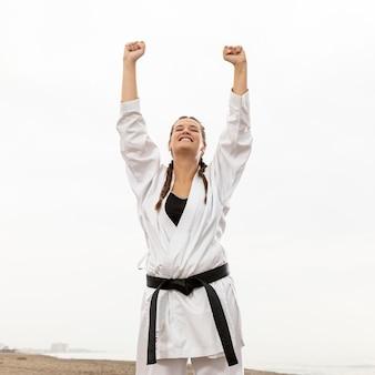 Glückliches junges mädchen im karatekostüm