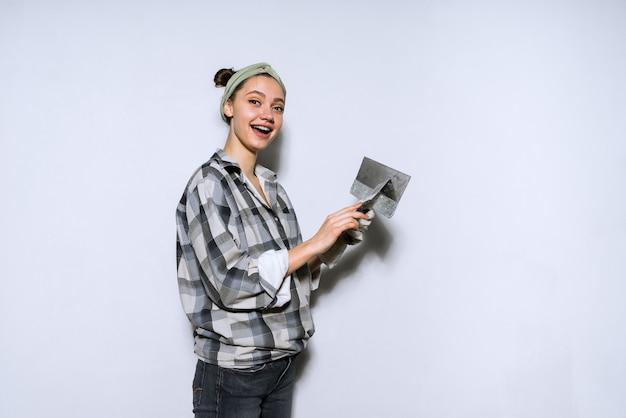 Glückliches junges mädchen im karierten hemd säumt die wand mit einem spachtel in ihrer neuen wohnung