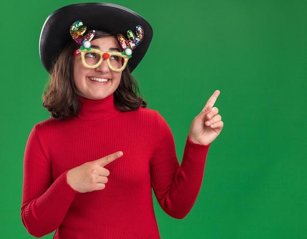 Glückliches junges mädchen im roten pullover, der lustige brille und schwarzen hut trägt, der oben schaut