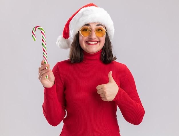 Glückliches junges mädchen im roten pullover und in der weihnachtsmannmütze, die brille hält, die zuckerstange hält, die kamera lächelnd zeigt, daumen hoch stehend über weißem hintergrund