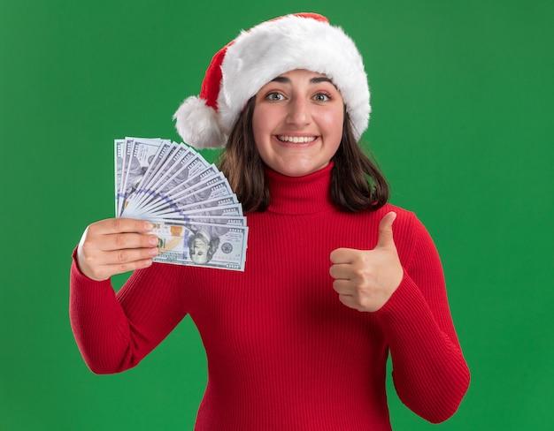 Glückliches junges mädchen im roten pullover und in der weihnachtsmannmütze, die das geld hält, das fröhlich lächelnd zeigt daumen hoch, die über grüner wand stehen