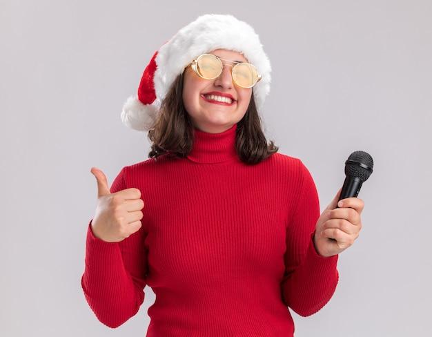Glückliches junges mädchen im roten pullover und in der weihnachtsmannmütze, die die brille hält, die das mikrofon hält, das kamera betrachtet, die fröhlich daumen zeigt, die oben über weißem hintergrund stehen
