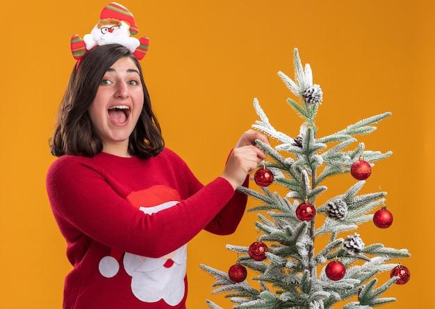 Glückliches junges mädchen im weihnachtspullover, der lustiges stirnband mit lächeln auf gesicht trägt, das neben einem weihnachtsbaum steht, der weihnachtskugeln über orange wand hängt
