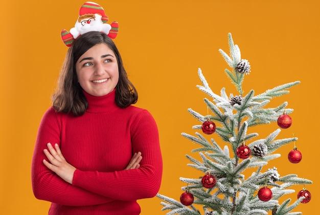 Glückliches junges mädchen im weihnachtspullover, der lustiges stirnband trägt, das mit lächeln auf gesicht neben einem weihnachtsbaum über orange hintergrund beiseite schaut
