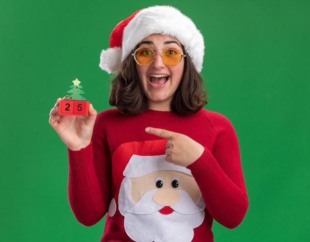 Glückliches junges mädchen im weihnachtspullover, der weihnachtsmütze und gläser hält, die spielzeugwürfel mit der nummer fünfundzwanzig zeigen, die mit zeigefinger darauf zeigen und fröhlich über grüner wand stehend lächeln