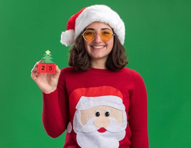 Glückliches junges mädchen im weihnachtspullover, der weihnachtsmütze und gläser hält, die spielzeugwürfel mit nummer fünfundzwanzig mit lächeln auf gesicht halten, das über grüner wand steht