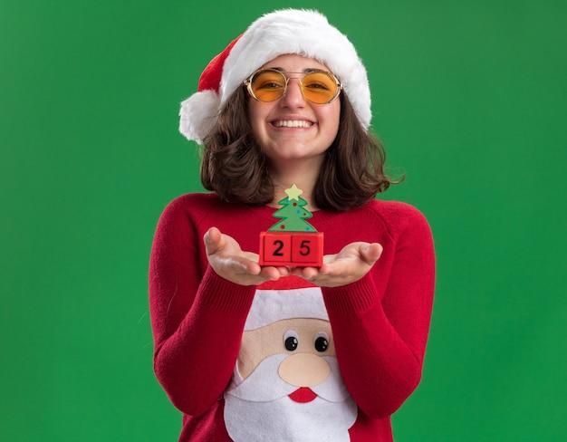 Glückliches junges mädchen im weihnachtspullover, der weihnachtsmütze und gläser trägt, die spielzeugwürfel mit nummer fünfundzwanzig lächelnd breit stehend über grüner wand zeigen