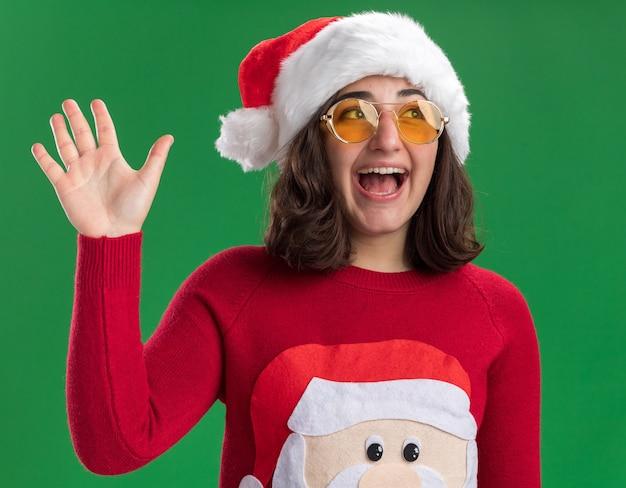 Glückliches junges mädchen im weihnachtspullover santa hut und in den gläsern, die beiseite lächelnd fröhlich winkend mit der hand stehen über grüner wand schauen