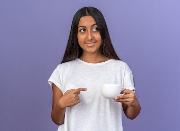 Glückliches junges mädchen im weißen t-shirt, das eine weiße tasse hält, die mit dem zeigefinger darauf zeigt und mit einem lächeln auf dem gesicht auf blauem hintergrund beiseite schaut