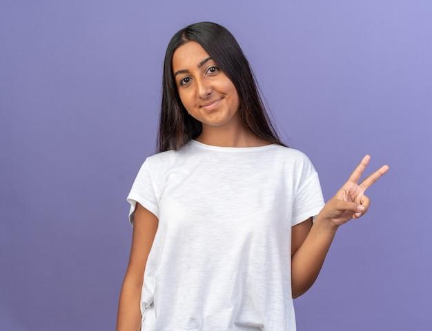 Glückliches junges mädchen im weißen t-shirt, das mit einem lächeln im gesicht in die kamera schaut und ein v-zeichen auf blauem hintergrund zeigt