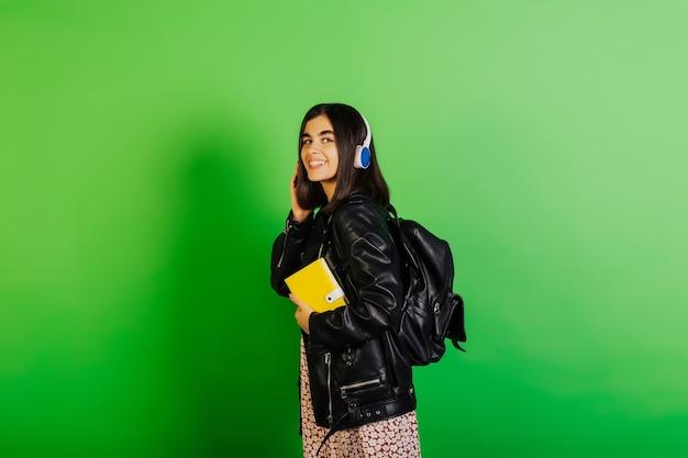 Glückliches junges mädchen in der schwarzen lederjacke und im rucksack hält gelben notizblock und hört die musik im drahtlosen kopfhörer, isoliert auf grüner oberfläche.