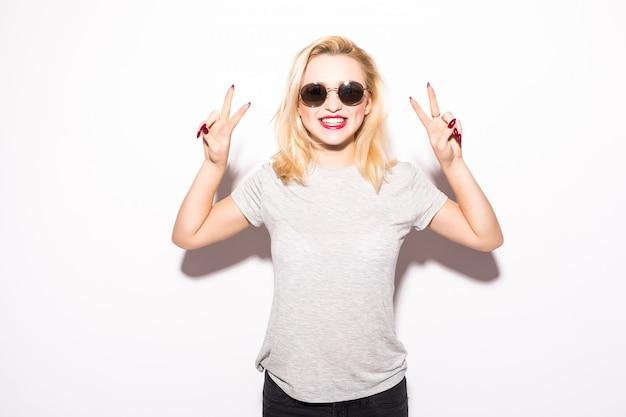 Glückliches junges mädchen in der sonnenbrille, die friedenszeichen zeigt