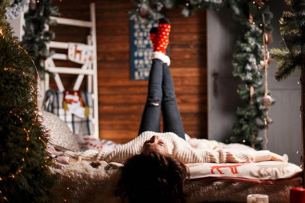 Glückliches junges mädchen in einem gestrickten pullover und roten warmen socken liegt auf einem bett mit einer weihnachtsdekoration