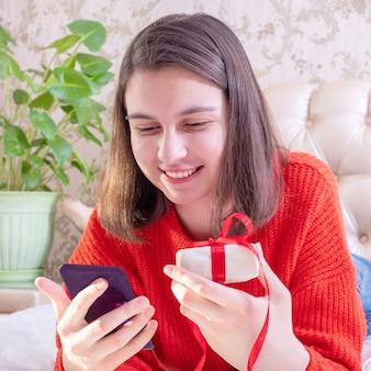 Glückliches junges mädchen in einem roten pullover, der ein geschenk hält und familie oder freunde mit einem smartphone, nahaufnahme, vorderansicht, quadrat gratuliert.