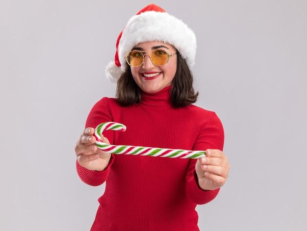 Glückliches junges mädchen in rotem pullover und weihnachtsmütze mit brille, die zuckerstange hält und canera mit einem lächeln im gesicht auf weißem hintergrund betrachtet