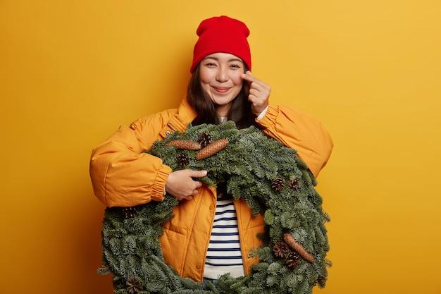 Glückliches junges mädchen macht koreanisch wie zeichen, drückt liebe und zuneigung aus, trägt roten hut und oberbekleidung, hält grünen handgemachten kranz, macht sich bereit für weihnachten