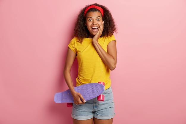 Glückliches junges mädchen mit afro-haaren hält skateboard, hat spaß mit freund beim skaten, genießt aktive ruhe