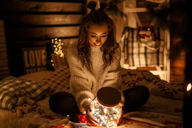 Glückliches junges mädchen mit einem haarschnitt in einem gestrickten weinlesepullover hält ein magisches glas mit lichtern an heiligabend