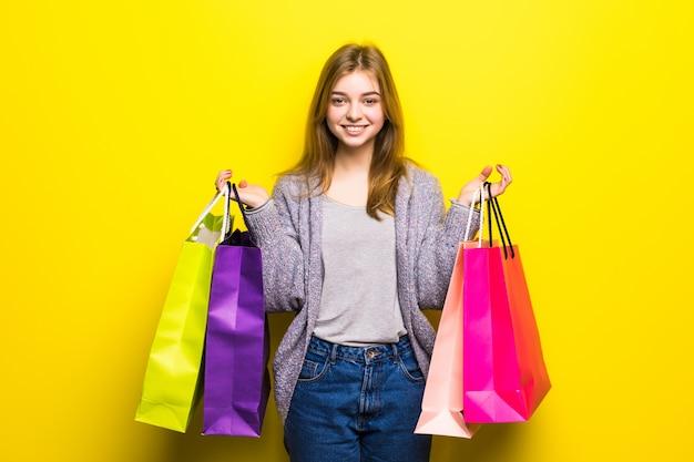 Glückliches junges mädchen mit einkaufstüten isoliert