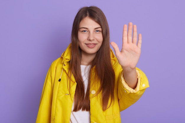 Glückliches junges mädchen mit langen haaren, die stoppgeste mit handfläche zeigen und lächelnd gelbe jacke tragen