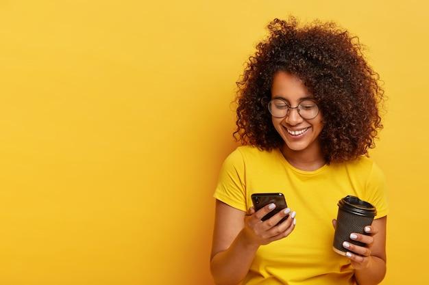 Glückliches junges mädchen mit lockigem haar, hält modernes handy, kaffee zum mitnehmen, bestellt taxi über online-bewerbung, schreibt sms, trägt gelbe kleidung. menschen, moderner lebensstil und technologie