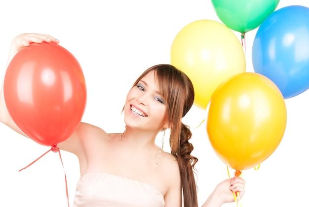 Glückliches junges mädchen mit luftballons über weiß