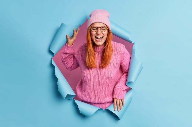 Glückliches junges mädchen mit natürlichen roten haaren hat spaß und kichert positiv kann nicht aufhören zu lachen hört etwas sehr lustiges schließt augen trägt rosa kleidung.