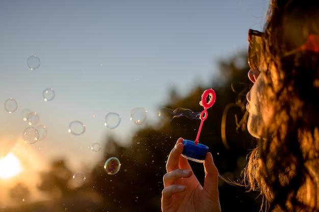 Glückliches junges mädchen mit seifenblasen im herbst bei sonnenuntergang.