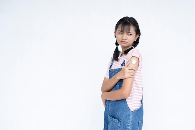 Glückliches junges mädchen nach der impfung asiatisches mädchen auf weißem hintergrundstudentenmedizinischem konzept