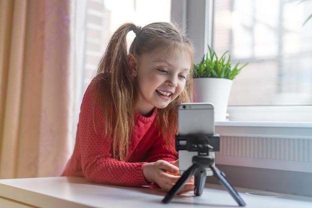 Glückliches junges mädchen schaut auf das telefon und kommuniziert online zu hause