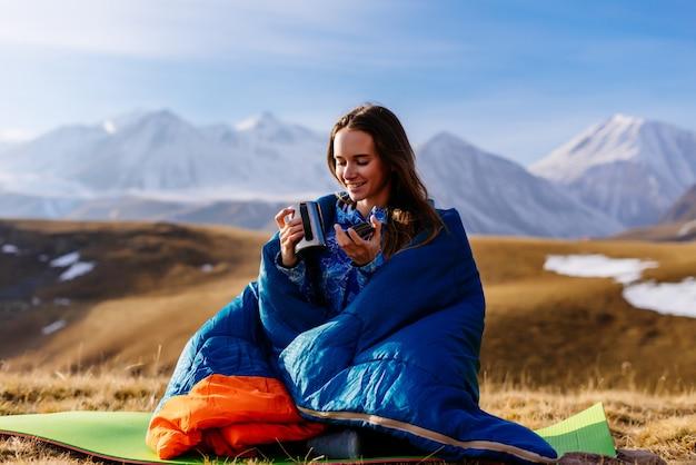 Glückliches junges mädchen sitzt in einem blauen schlafsack vor dem hintergrund der kaukasischen berge, trinkt heißen tee