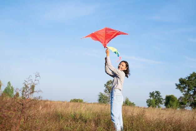 Glückliches junges mädchen spielt drachen auf der wiese mit blauem himmel