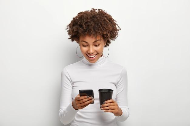 Glückliches junges mädchen surft internet auf handy, verbunden mit kostenlosem wifi, trinkt kaffee zum mitnehmen, trägt lässigen rollkragenpullover