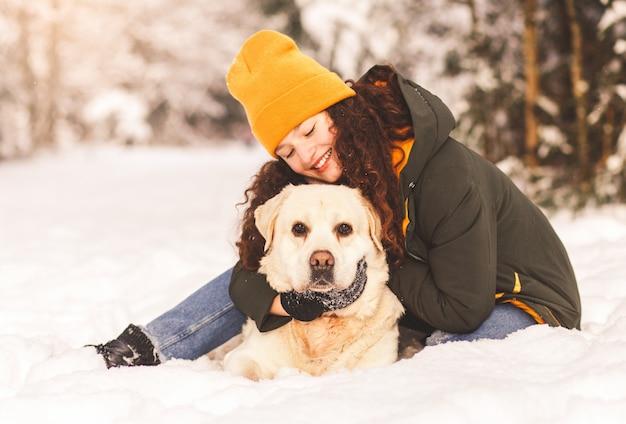 Glückliches junges mädchen umarmt ihren weißen labrador-hund im winter draußen