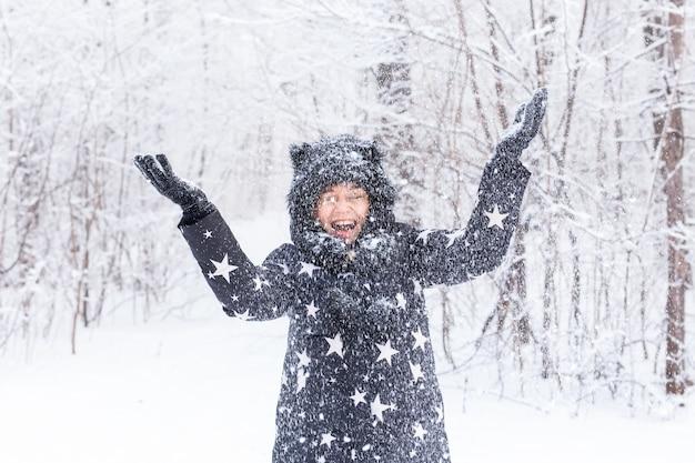 Glückliches junges mädchen wirft einen schnee in einem winterwald hoch