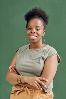 Glückliches junges modemodell der afrikanischen ethnie, das die arme an der brust verschränkt