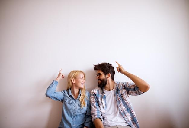 Glückliches junges modernes paar, das gegen die wand steht.