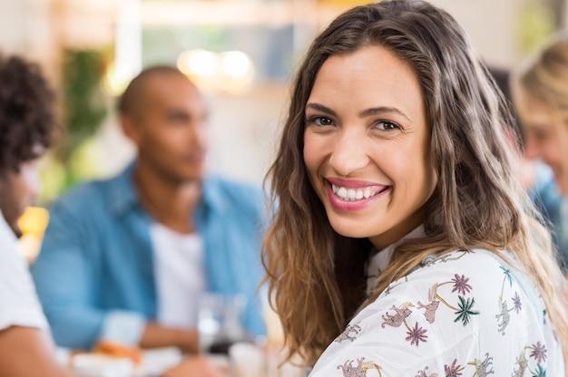 Glückliches junges multiethnisches frauengesicht, das mit ihren freunden in der wand frühstückt