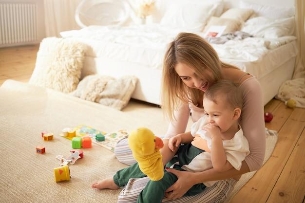 Glückliches junges mutterspiel und niedliches kleines kind, das auf boden spielt. blondes weibliches babysittendes entzückendes kind, das auf teppich im schlafzimmer hält, das gelbes entenspielzeug hält. mutterschafts- und kinderbetreuungskonzept
